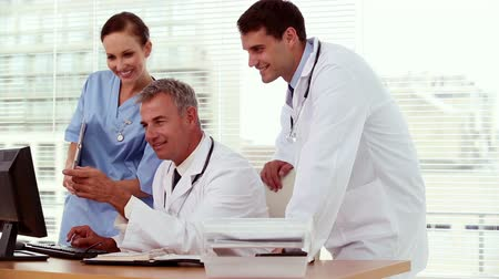 сотрудники : Smiling doctor showing something to his colleagues on his computer in medical office