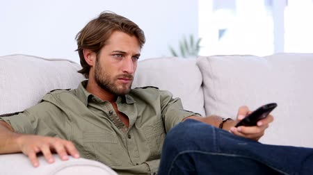 assistindo : Attractive man sitting on couch watching TV and holding remote