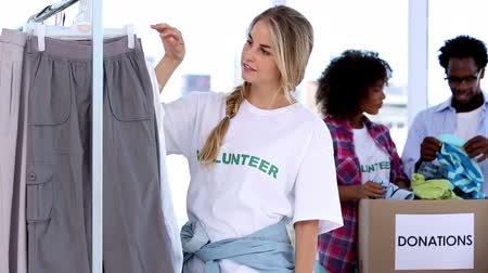 dobrovolník : Pretty volunteer looking at clothes while her colleagues are speaking behind her