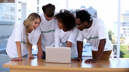 dobrovolník : Group of young volunteers using laptop together