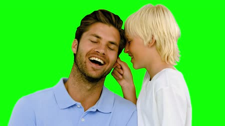 тайна : Son pinching the ear of his father on green screen in slow motion Стоковые видеозаписи