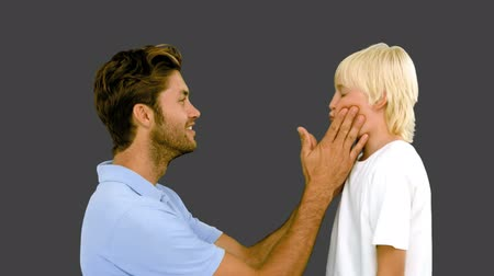 bochecha : Man pressing inflated cheeks of his son on grey background in slow motion Stock Footage