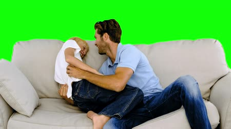 oğlum : Father tickling his son on the sofa on green screen in slow motion