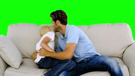 łaskotanie : Father tickling son on the sofa on green screen in slow motion