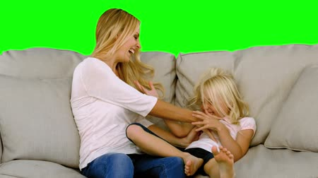łaskotanie : Mother tickling her daughter in slow motion on green screen Wideo