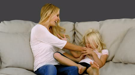 łaskotanie : Mother tickling her daughter on sofa in slow motion on grey screen