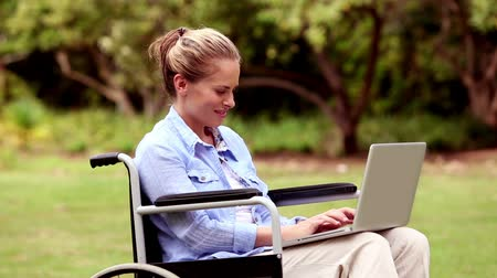 rokkant : Attractive woman in a wheelchair using her laptop in a park