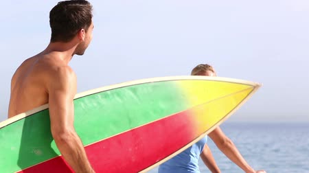 surf : Surfer holding surfboard and speaking with his friend