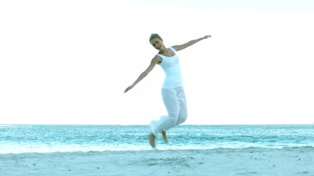braços levantados : Girl Jumping on the beach in slow motion