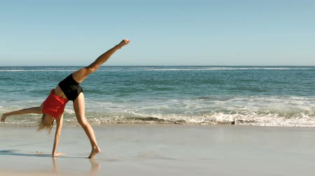 gymnasta : Womandoing a cartwheel on the beach in slow motion