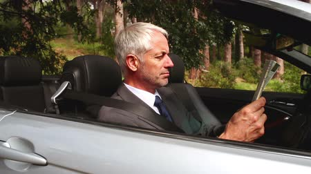 confuso : Confused businessman looking at map in his convertible car   Vídeos