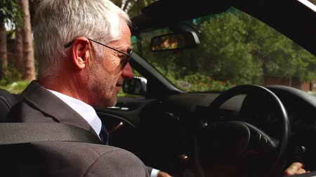 nóbl : Businessman wearing sunglasses and sitting in his convertible car