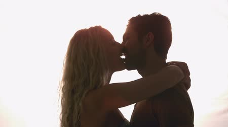 namorado : Couple kissing against sunlight in slow motion