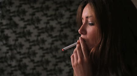 cigarettes : Attractive brunette smoking cigarette in dark room