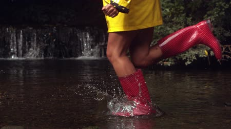 csizma : Woman in pink rubber boots running in water and splashing Stock mozgókép