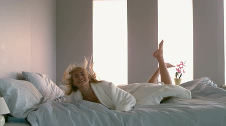almofada : Cheerful blonde jumping on bed in bright bedroom Vídeos