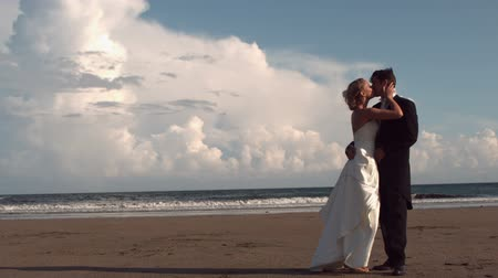 подвенечное платье : Happy newlywed couple kissing on the beach in slow motion