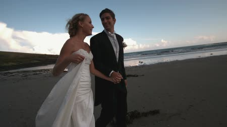 İrlanda : Cheerful newlywed couple walking and kissing on the beach in slow motion Stok Video