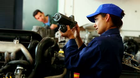 mechanika : Young pretty woman working in a garage wearing workclothes Dostupné videozáznamy