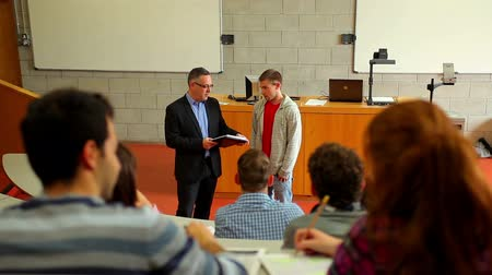 лекция : Student talking to lecturer in lecture hall at the university