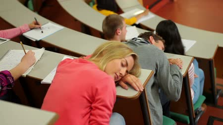 лекция : Student asleep at desk in lecture hall at the university