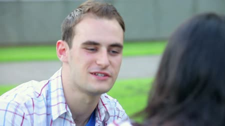 chatting : Students having a chat on the lawn on college campus Stock Footage