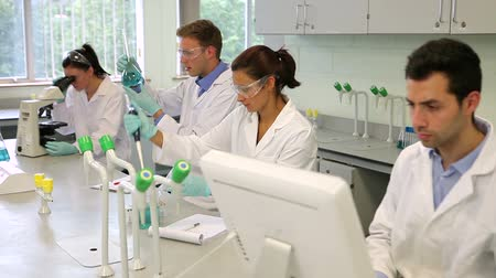 ученый : Team of focused young science students working together in the lab at the university