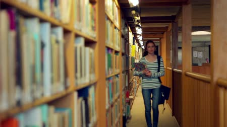 könyvtár : Student walking through the library in college