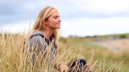 kaukázusi : Blonde woman relaxing in the dunes at the beach Stock mozgókép
