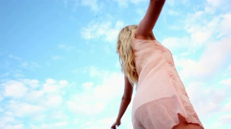 ventoso : Blonde woman spinning joyfully on a clear day
