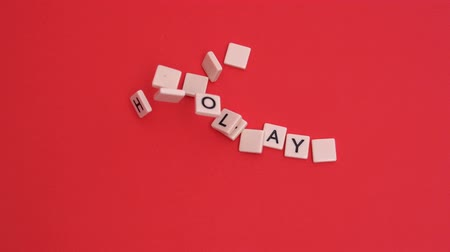 holidays : Letter tiles moving to spell out happy holidays on red background in slow motion