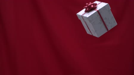 přítomný : Christmas present thrown into the air red background in slow motion