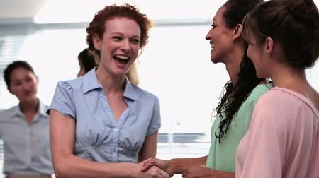 рукопожатие : Businesswomen shaking hands after a seminar and smiling in office