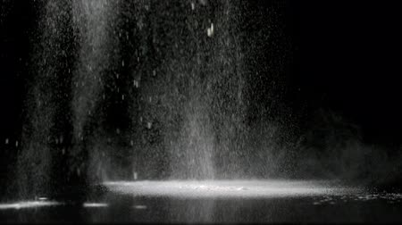 мучной : Flour sprinkled onto black surface in slow motion