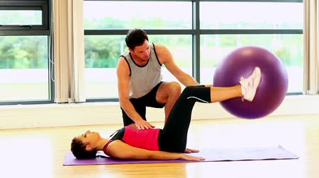 eğitici : Sporty slender woman lifting fitness ball with her legs being watched by coach Stok Video
