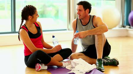 eğitici : Two sporty friends sitting on floor in fitness hall chatting