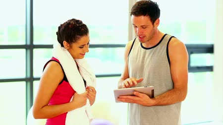 koç : Handsome coach talking to sporty woman in fitness hall