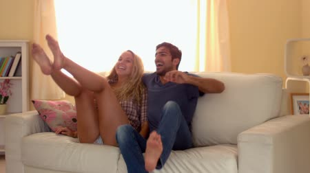 İrlanda : Young attractive couple jumping on couch in bright living room