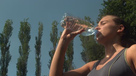 hidrasyon : Athletic sporty woman drinking a bottle of water in a park in slow motion