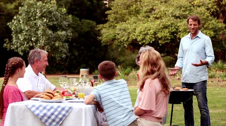 grillowanie : Family eating outdoors and preparing the barbecue
