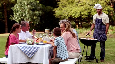 preparing : Happy family eating in a park and father cooking barbecue