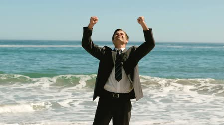 poça de água : Joyful businessman on the beach in slow motion Stock Footage