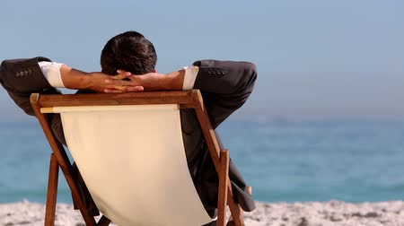krawat : Businessman relaxing on the beach and looking at the sea Wideo