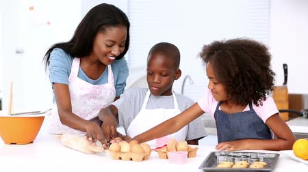 black : Mother and children making pastry and wearing aprons at home in kitchen