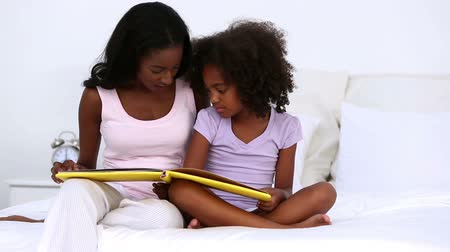 ler : Mother and her daughter reading book on a bed at home