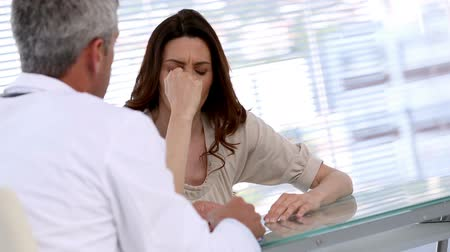ideges : Doctor announcing an important disease to his patient then comforting her