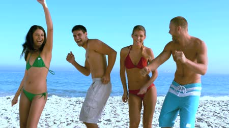 companionship : Group of friends dancing on the beach in slow motion