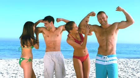 мышцы : Women feeling biceps of muscled men on the beach in slow motion