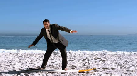 suit and tie : Businessman balancing on surfboard on the beach in slow motion