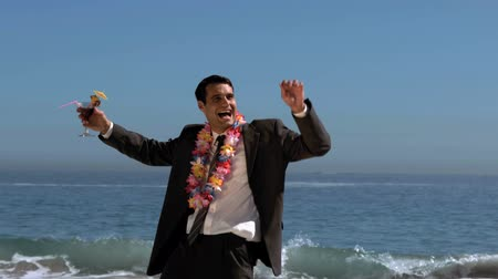 coquetel : Attractive businessman dancing on the beach while he is holding a cocktail in slow motion